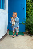 Cute baby boy carrying kitten. rural exterior Stock Photography