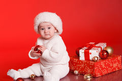 Cute baby boy with christmas decorations over red Stock Image