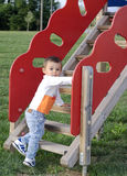 Cute baby boy on the climb stairs. Active baby boy learns to climb wooden slide stairs on the playground stock photography