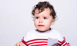 Cute baby boy crying. Little child in pain, suffering, teething, refusing and crying. Cute sad baby throwing a tantrum.  Little child looking away Royalty Free Stock Images