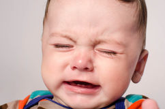 Cute baby boy crying. Little child in pain, suffering, teething, refusing and crying. Cute sad baby throwing a tantrum. Baby wants up in the arms to be held Royalty Free Stock Image