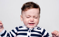 Cute baby boy crying. Little child in pain, suffering, teething, refusing and crying. Cute sad baby throwing a tantrum. Baby wants up in the arms to be held Stock Photos