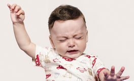 Cute baby boy crying raising his hands up. Little child in pain, suffering, teething, refusing and crying. Cute sad baby throwing a tantrum Royalty Free Stock Photography