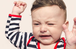 Cute baby boy crying raising his hands up. Little child in pain, suffering, teething, refusing and crying. Cute sad baby throwing a tantrum Royalty Free Stock Photos