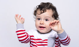 Cute baby boy crying raising his hands up. Little child in pain, suffering, teething, refusing and crying. Cute sad baby throwing a tantrum. Baby wants up in Stock Photography