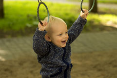 Cute baby boy doing sport in the park. Funny toddler workouts on the athletic rings.  Royalty Free Stock Image