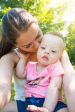 Cute baby boy with Down syndrome and his young mother in summer day. On nature royalty free stock images