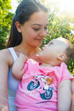 Cute baby boy with Down syndrome and his young mother in summer day. On nature royalty free stock image