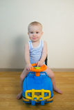 Cute Baby boy driving a toy car at home.  Royalty Free Stock Images