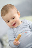Cute baby boy eating a biscuit Stock Photography