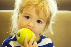 Cute baby boy eating green apple Royalty Free Stock Image