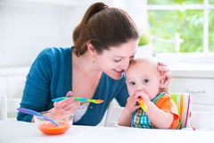 Cute baby boy eating his first solid food with his mother. Young attractive mother feeding her cute baby son, giving him his first solid food, healthy vegetable Royalty Free Stock Photo