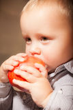 Cute baby boy eating red apple fruit Royalty Free Stock Image