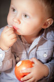 Cute baby boy eating red apple fruit Stock Image