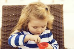 Cute baby boy eating tasty ice cream in outdoor cafe. Cute baby boy, small, little child with long, blond hair in blue, striped clothes eating tasty ice cream stock photography
