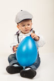 Cute baby boy with eyeglasses and hat playing with balloon Royalty Free Stock Images