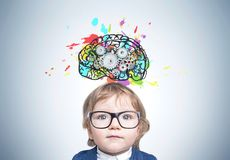 Cute baby boy in glasses, brain cogs. Close up of a serious boy wearing a suit and glasses and standing near a gray wall with a colorful brain sketch with gears stock image