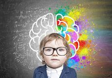 Cute baby boy in glasses and colorful brain sketch. Close up portrait of a cute little boy in a blue business suit standing near a blackboard with formulas and a stock photo