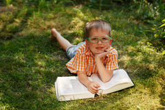 Cute baby boy with glasses lying on green grass, reading the book in summer day Royalty Free Stock Images