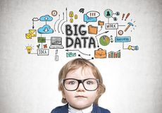 Cute baby boy in glasses and suit, big data. Cute little boy wearing a suit and glasses standing near a concrete wall with a big data sketch on it Royalty Free Stock Photo