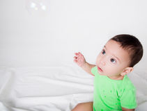 Cute baby boy in green clothing looking upwards at Stock Image