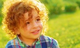 Cute baby boy on green field. Closeup portrait of cute baby boy with curly hair on green field, having fun outdoors, enjoying summer vacation, happy childhood Royalty Free Stock Image