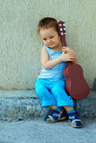 Cute baby boy with guitar sitting against wall. Cute baby boy with guitar sitting against the concrete wall Stock Photography