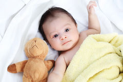 The cute baby boy is happy with yellow blanket and doll bear lovely friend on the white bed. Family Lovely Concept stock photo