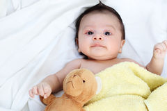 The cute baby boy is happy with yellow blanket and doll bear lovely friend on the white bed. Family Lovely Concept royalty free stock image