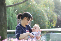Cute baby boy and  his mother. In park with bubbles inbackground Stock Photography