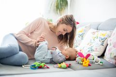 Cute baby boy and his mother, lying on the couch in living room. Playing with toys, activity for early infant development Stock Image