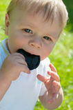 Cute baby boy holding lens cover on his mouth Royalty Free Stock Photo
