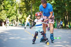 Cute baby boy with inline skating instructor in the park learini Royalty Free Stock Images