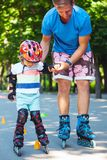 Cute baby boy with inline skating instructor in the park learini Royalty Free Stock Photo