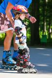 Cute baby boy with inline skating instructor in the park learini Royalty Free Stock Photography