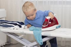 Cute baby boy with iron. Funny toddler ironing clothes.  royalty free stock photos