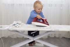 Cute baby boy with iron. Funny toddler ironing clothes.  royalty free stock images