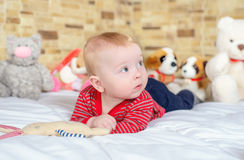 Cute baby boy in jeans and striped t-shirt lying bed looking up Royalty Free Stock Photos