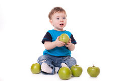 Cute baby boy kid eating and playing with green apples Royalty Free Stock Images