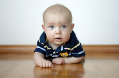 Cute Baby Boy Laying On His Tummy. On a hardwood floor with an expression of surprise Stock Photo