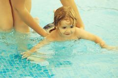 Cute baby boy learns to swim with mothers help. Cute happy baby boy with wet blond hair learns to swim with mothers help in outdoor pool water on sunny summer royalty free stock images