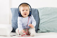 Cute baby boy listening music at headphones. stock photography