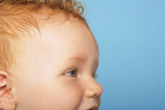Cute Baby Boy Looking Away. Side view of cute baby boy looking away on blue background Stock Photo