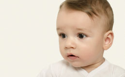 Cute baby boy looking to the side surprised. Royalty Free Stock Photography