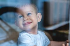 Cute baby boy looking in the window glass. Loneliness of children and waiting for kindness. Orphanage and orphans royalty free stock image