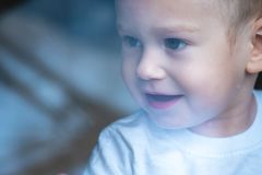 Cute baby boy looking in the window glass with reflection. Loneliness of children. Orphanage and orphans royalty free stock photography