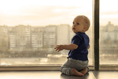Cute baby boy looking through the window to the rainy big city. Infant boy waiting for the parents. Toddler kid sitting. Cute baby boy looking through the window stock photos