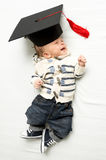 Cute baby boy lying in graduation hat on bed Stock Images