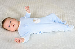 Cute baby boy is lying on the gray carpet Stock Images