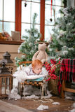 Cute baby boy lying on sled among Christmas decorations Royalty Free Stock Photography